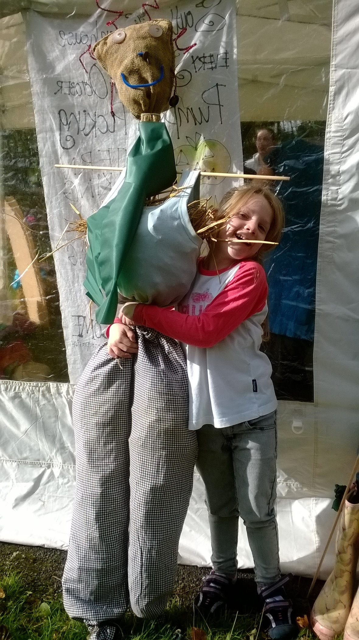 Girl hugging scraecrow made at Southsea Greenhouse