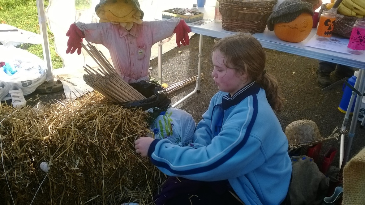 Girl getting straw for the scarecrow